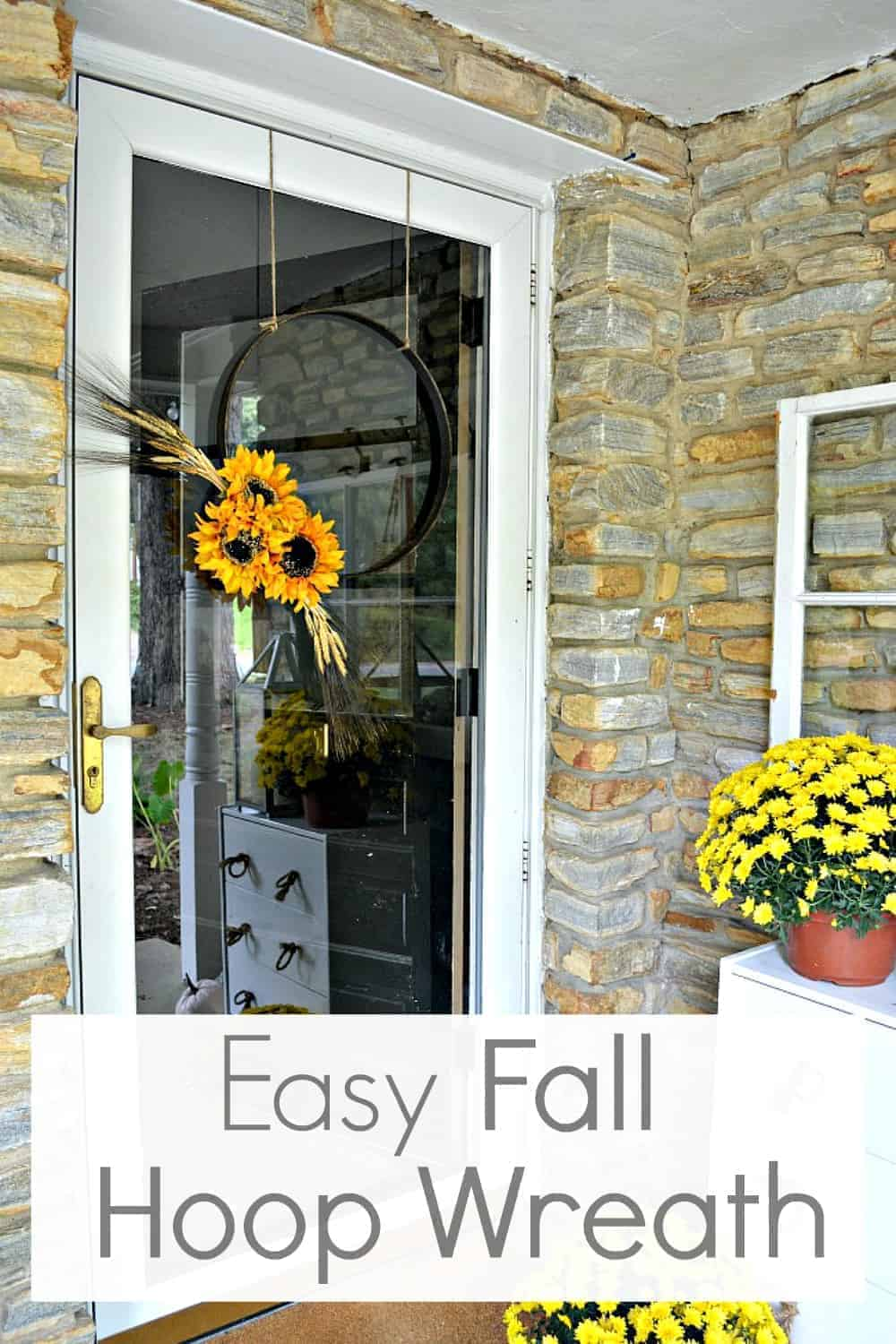 simple fall hoop wreath hanging on front door with mums surrounding it