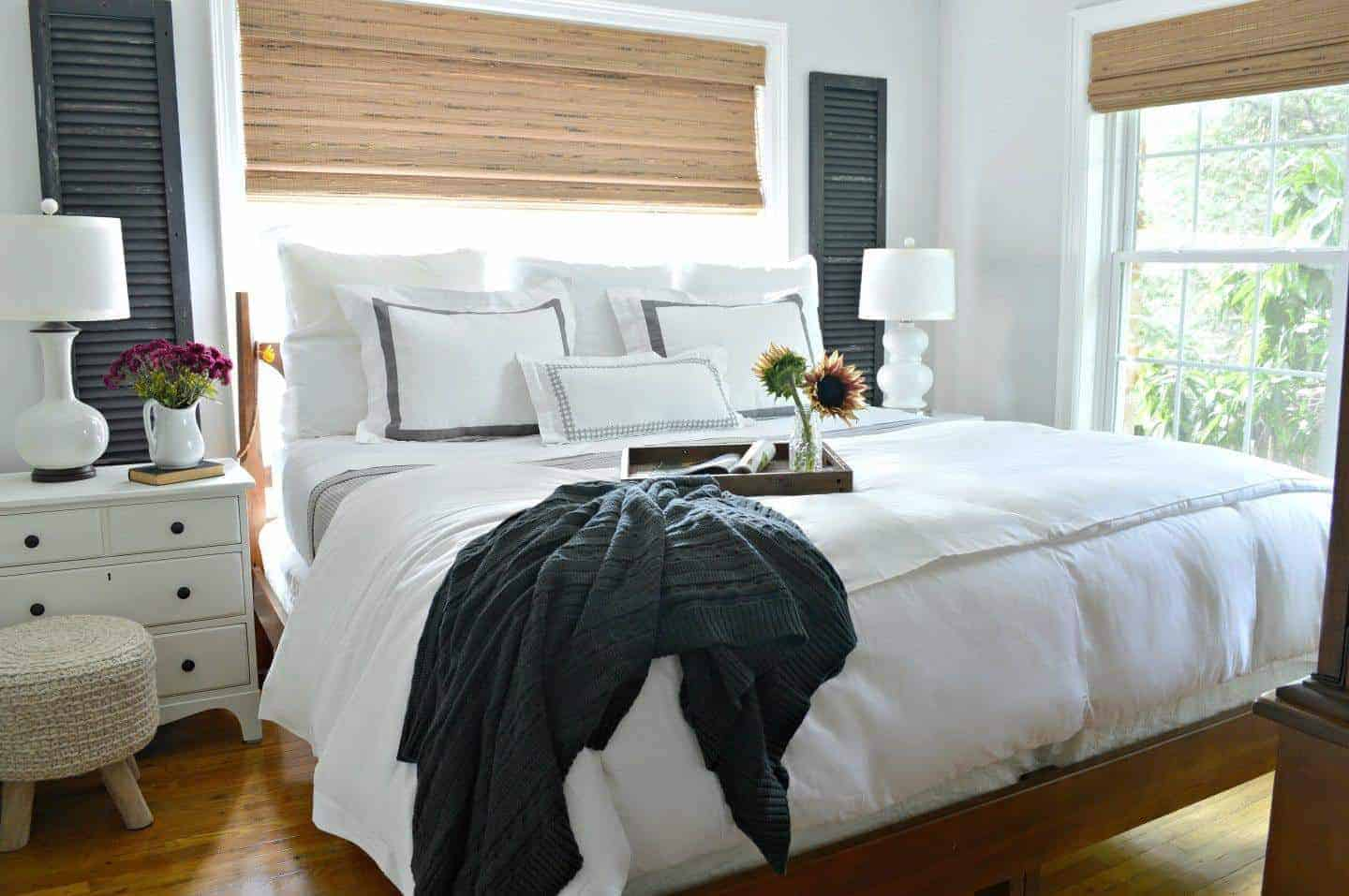 view of master bedroom with king size bed dressed with white linens and old wooden shutters hanging on wall next to window