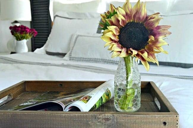 A vase of sunflowers on a bed