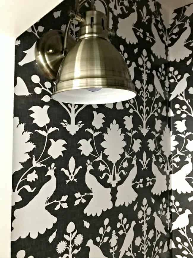 new gray wallpaper and gold light fixture in closet