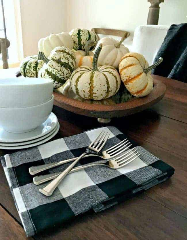 mini pumpkins stacked on top of fall table centerpiece made with a thrifted mirror, with black and white napkins and white dishes