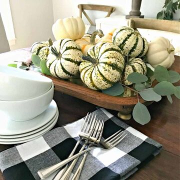 DIY fall centerpiece with gourds on top and black checked napkins