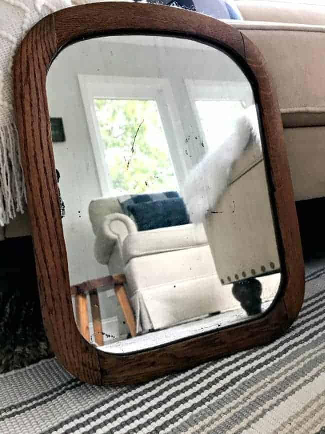 vintage wooden mirror propped up against couch