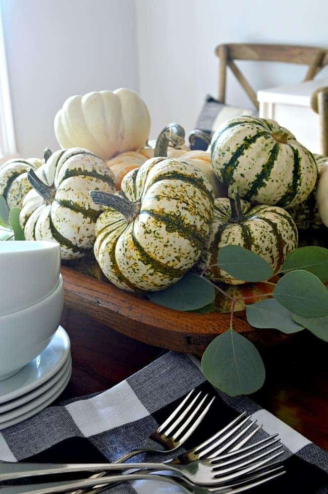 An easy and simple fall centerpiece made with an antique mirror, wood feet and lots of pumpkins. A quick and inexpensive way to add fall color and style to your table.