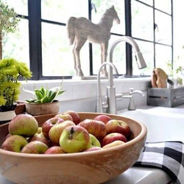 A bowl of fruit sitting on a kitchen counter