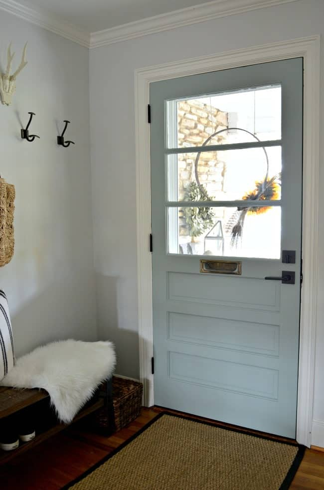 How to use a thrifted door to make a new farmhouse style front door for a 1946 stone cottage, by adding new hardware and painting it a beautiful color, Benjamin Moore Wythe Blue.