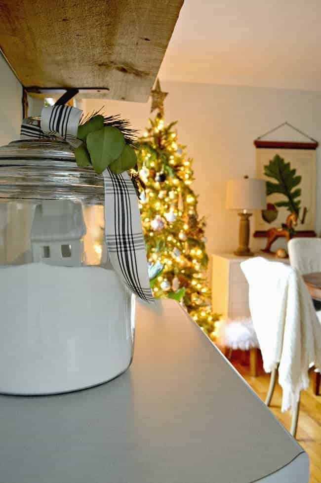 How to create a cozy cottage Christmas kitchen by using farmhouse touches like fresh greenery from the yard and black and white ribbon.