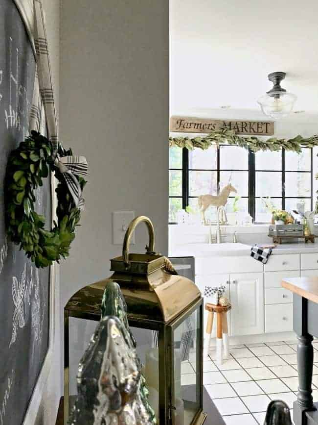 How to create a cozy cottage Christmas kitchen by using farmhouse touches like fresh greenery from the yard along with a touch of black and white.