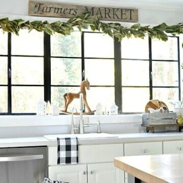 A kitchen with a sink and a window with garland