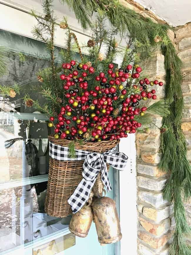 Creating a simple DIY Christmas front door basket, with bells and black buffalo check ribbon, to add holiday color to your front door.