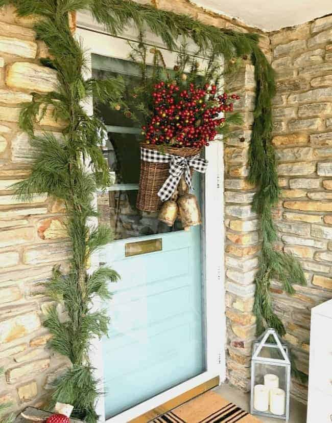 Creating a simple DIY Christmas front door basket, with berries and black buffalo check ribbon, to add holiday color and style to your front door.