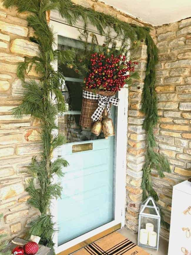 front door decorated with live garland and basket of berries