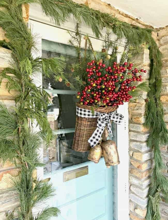 How to create a simple DIY Christmas front door basket, with bells and black buffalo check ribbon, to add holiday color and style to your front door.