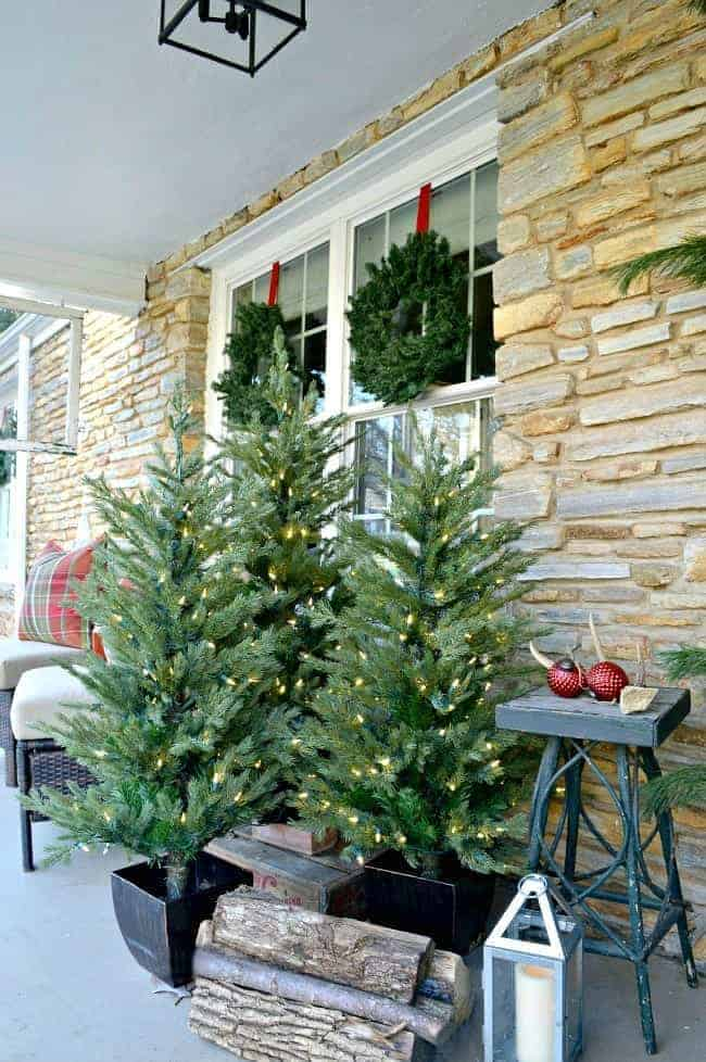 grouping of faux Christmas trees on front porch