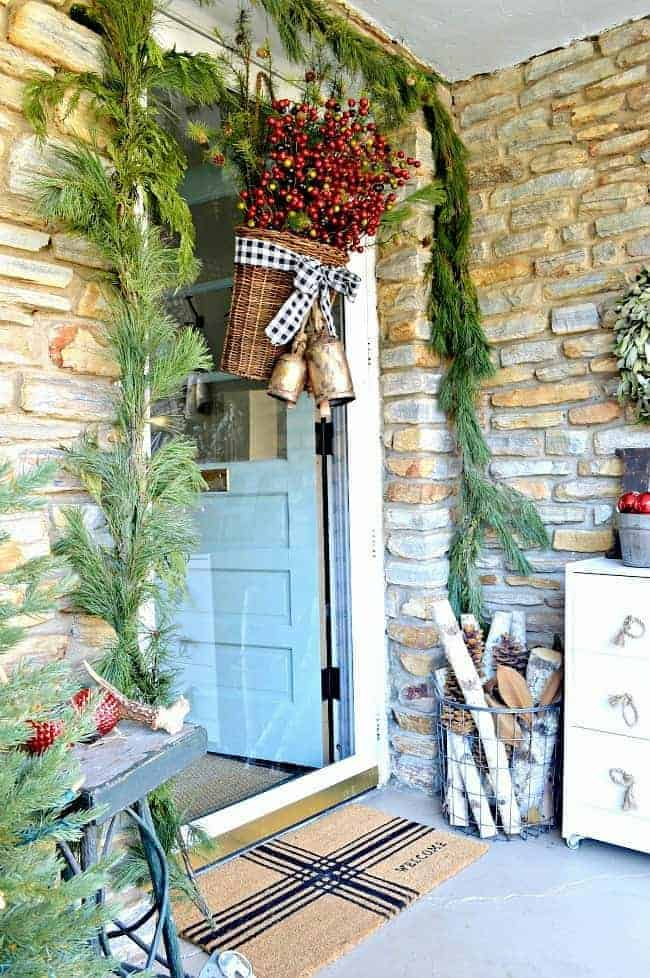 Add holiday color and style to your front door by creating a simple DIY Christmas front door basket, with berries and black buffalo check ribbon.