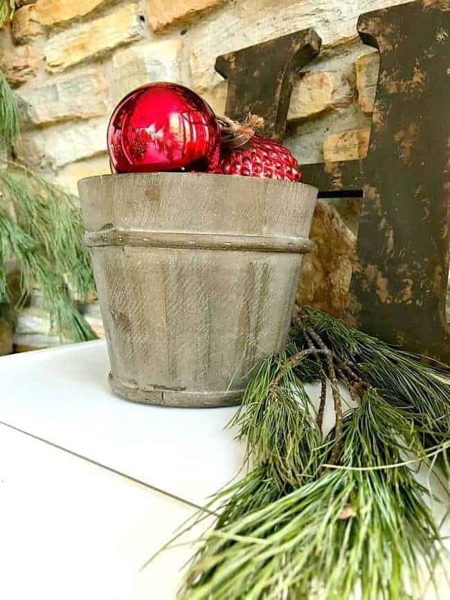 bucket of red ornaments on front porch