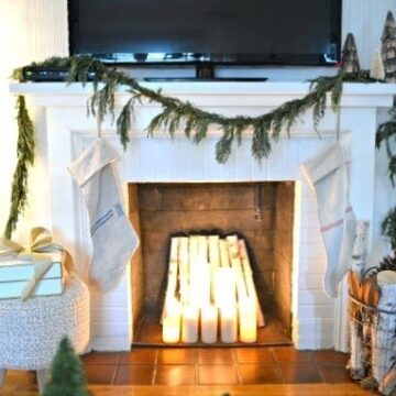 A room with a fireplace decorated for Christmas