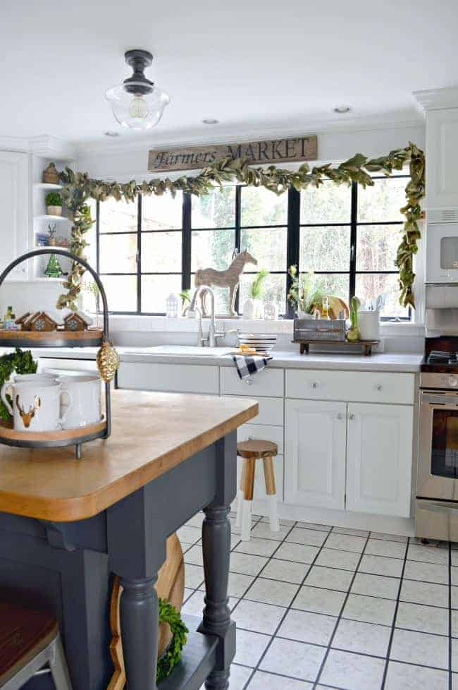 How to create a cozy cottage Christmas kitchen by using farmhouse touches like fresh greenery from the yard to make a live garland for a window.