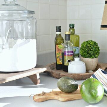 A close up of a cutting board and bottles of oil on the counter,