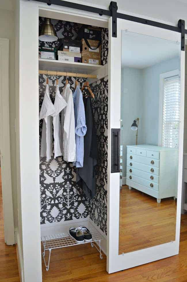 small closet with dark gray and white wallpaper and mirrored barn door