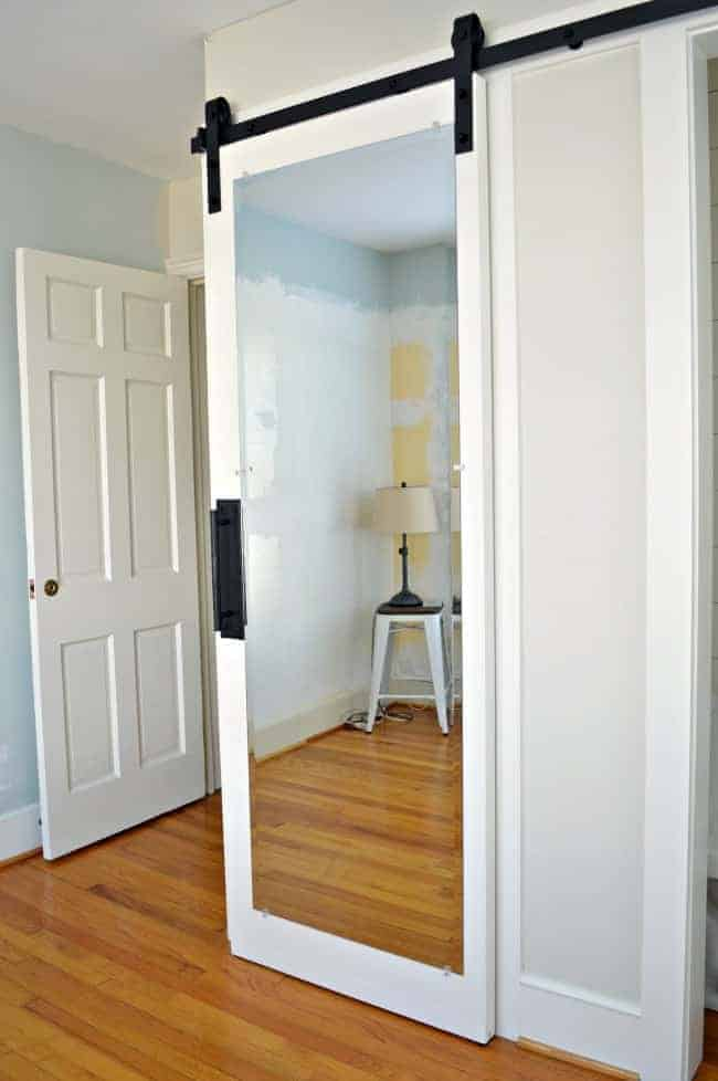 hanging white mirrored barn door with iron handle for bedroom closet