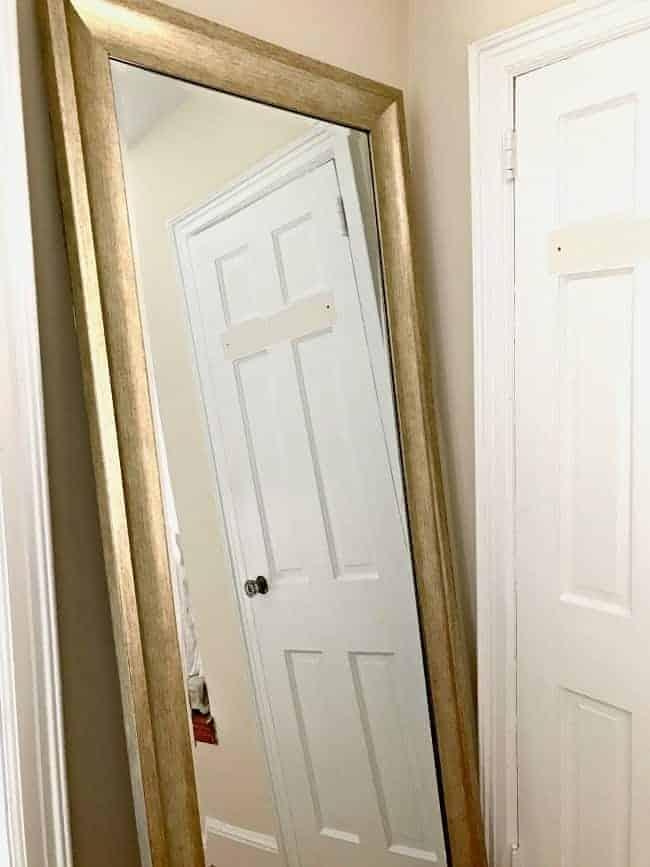 large leaning mirror with gold frame