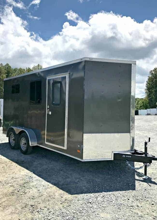 A gray enclosed landscape trailer with 2 windows and a door