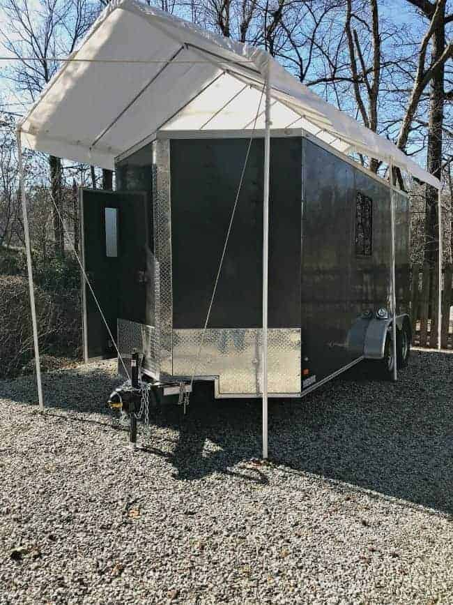 outside view of gray landscape camper with white awning over it