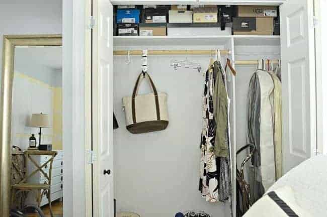 bedroom closet with clothes, shoe boxes and canvas bag