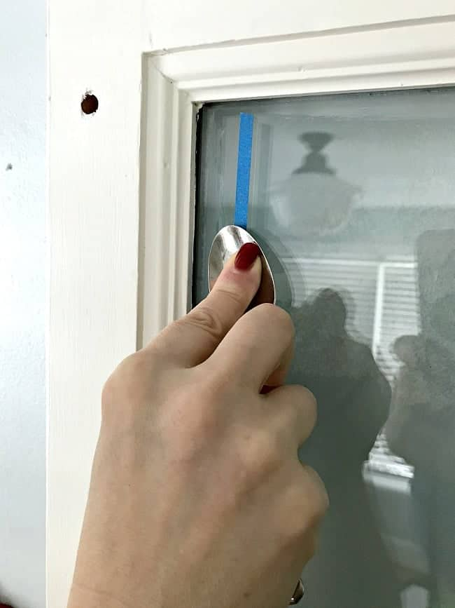 adding painter's tape to a bathroom door window and smoothing it out with a spoon