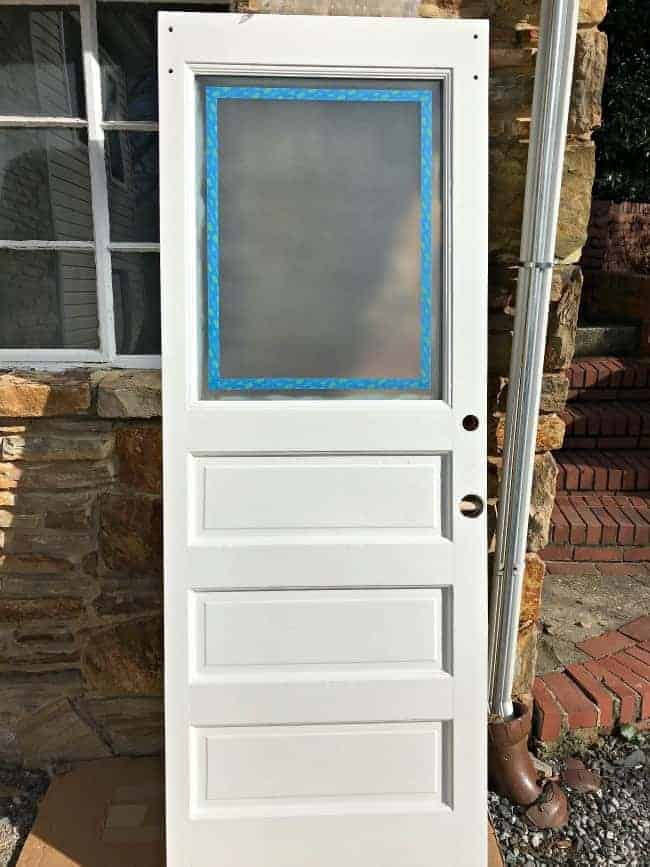 old white door with window taped with painter's tape and frosted