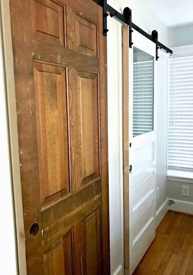 an old wooden door and white door hung with barn door hardware