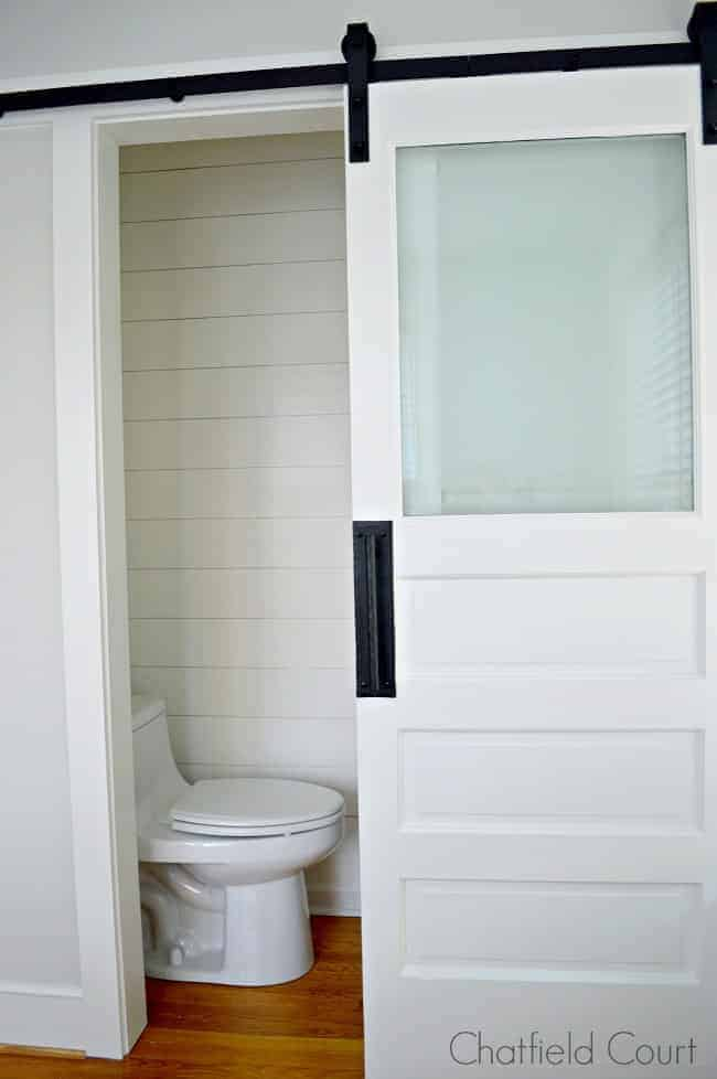 The best white paint colors and a barn door and toilet in tiny powder room
