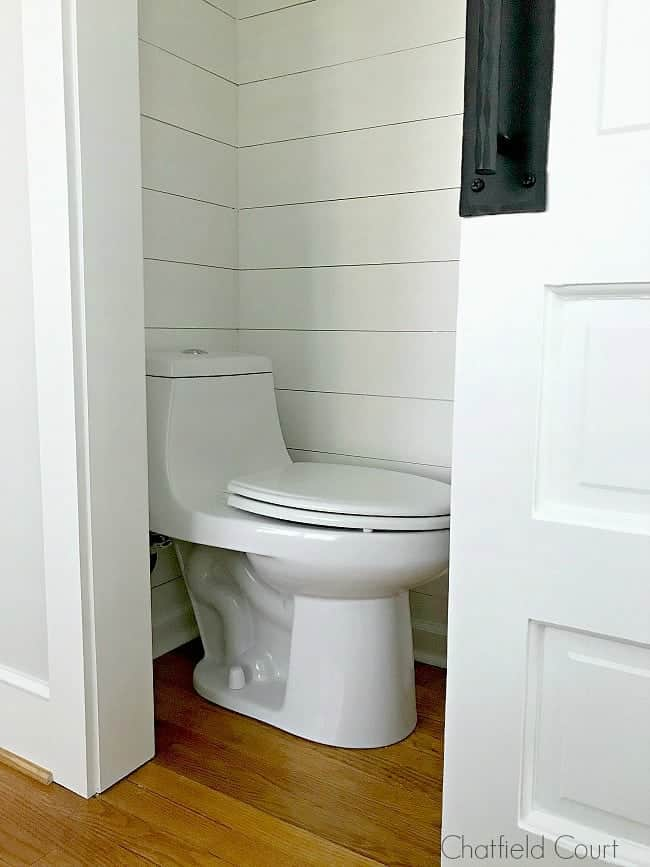 toilet in small powder room with shiplap walls