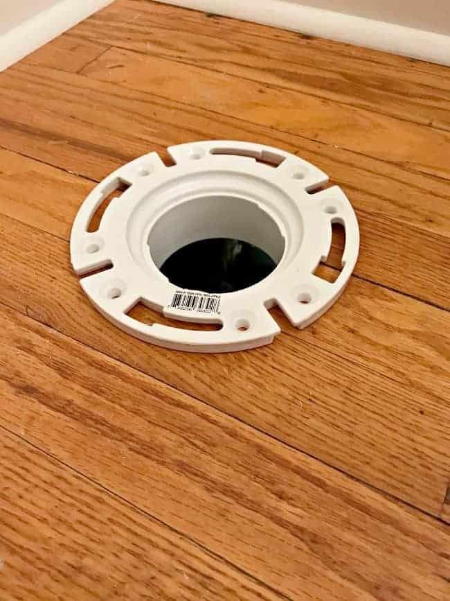 toilet bracket in hole in hardwood floor
