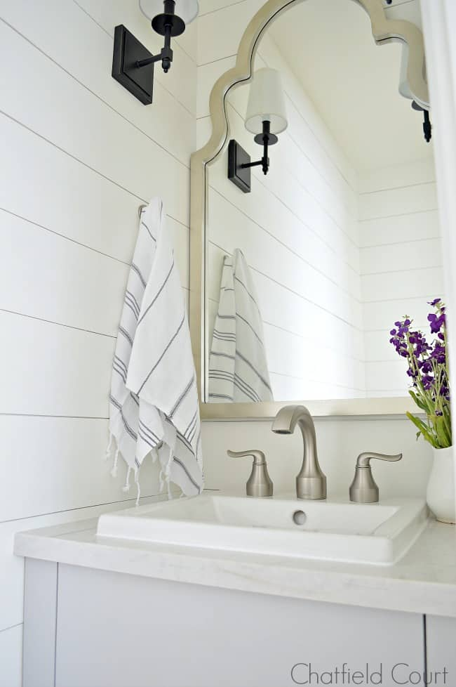 The best white paint colors and a small powder room with gray vanity and silver mirror