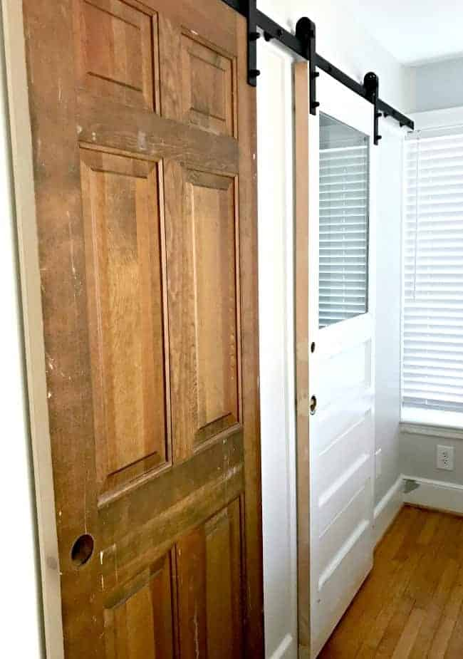 old doors hanging up on closet and bathroom barn door rail