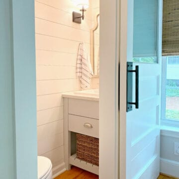 small powder room with vanity and shiplap walls