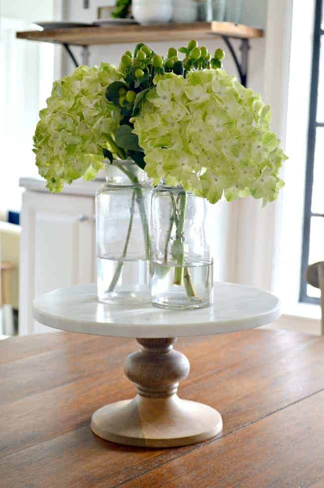 3 glass bottles with hydrangea on a marble cake stand in the middle of a wood table