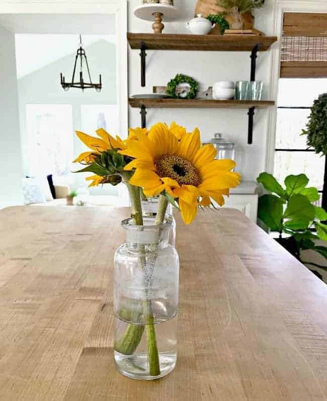 3 glass bottles with sunflowers in them on a kitchen island