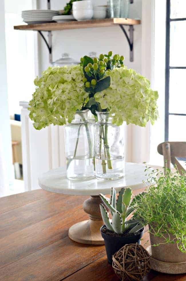 hydrangeas in glass bottles on a marble cake plate in the center of the table