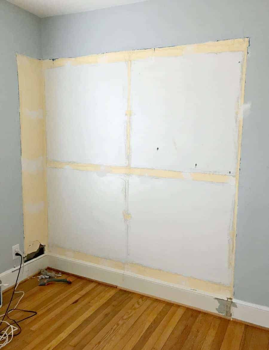 damaged wall in blue bedroom with holes and spackle