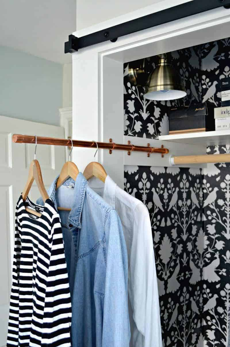 3 shirts hanging on copper pipe sliding clothes rod in small closet with bird wallpaper