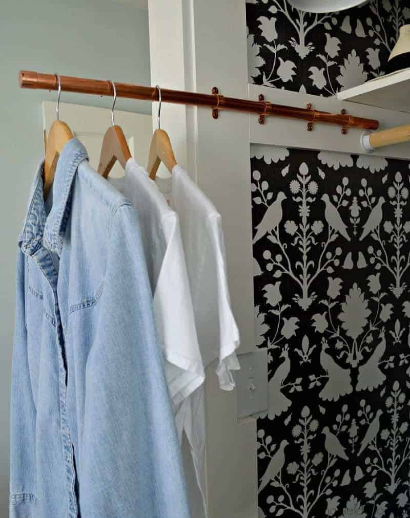 DIY copper pipe sliding clothes rod in wallpapered closet with 3 shirts hanging on it