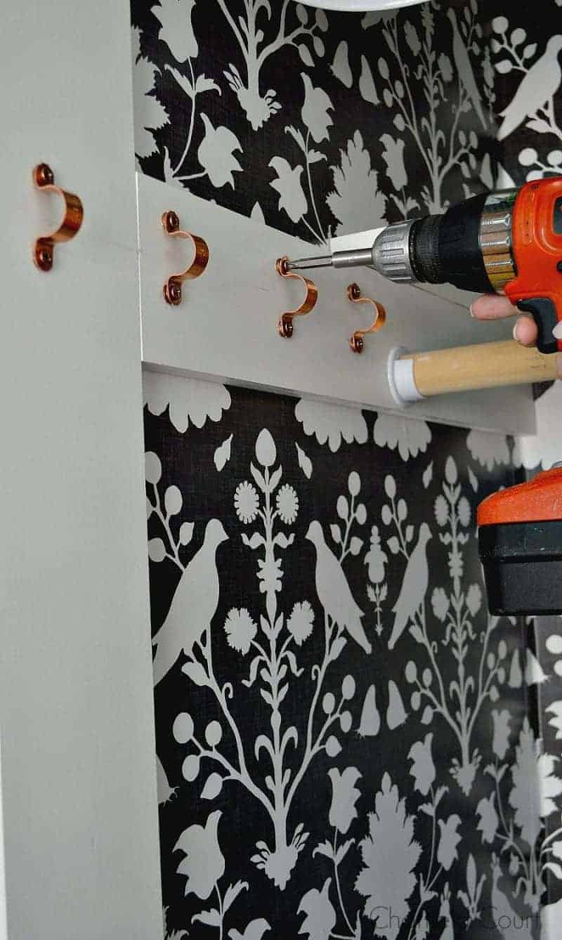 using drill to screw in copper painted screws in a closet