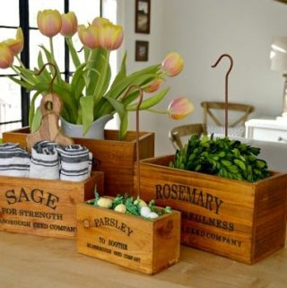 4 wooden herb boxes with tulips, linen napkins, green wreaths an Easter egg candy in them