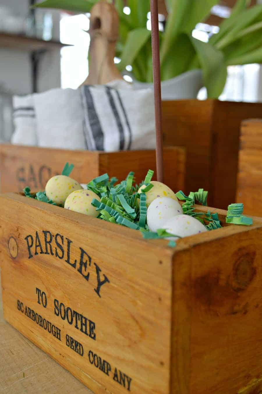 Parsley wooden herb box sitting on a butcher block island with candy eggs in green paper grass.