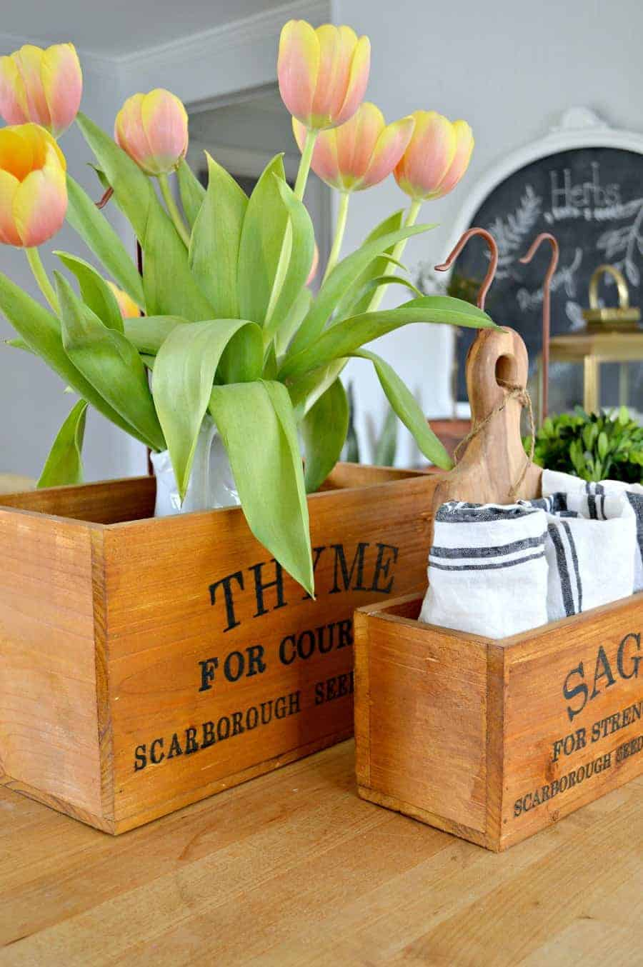Thyme and Sage wooden herb boxes sitting on a butcher block island with tulips and napkins in them.