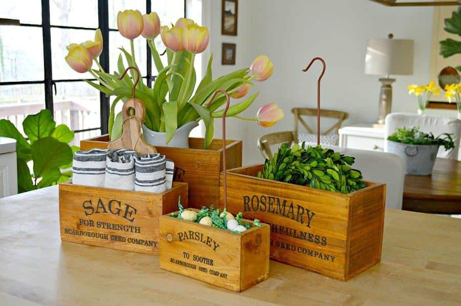 4 wooden herb boxes sitting on a butcher block island with tulips, napkins and green wreaths in them.