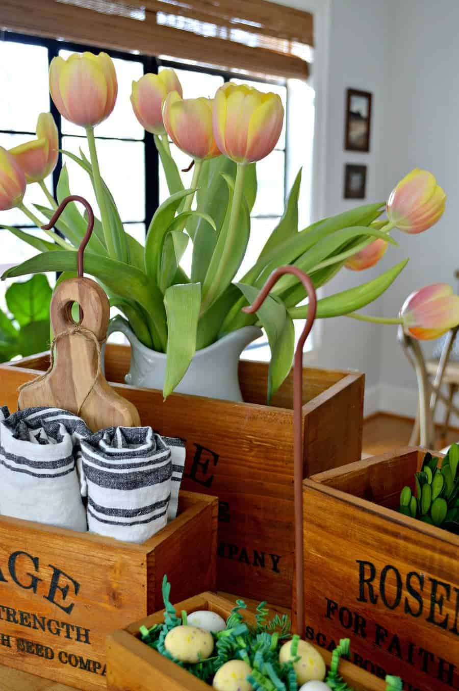 4 wooden herb boxes sitting on a butcher block island with tulips, napkins, candy eggs in green paper grass and green wreaths in them.